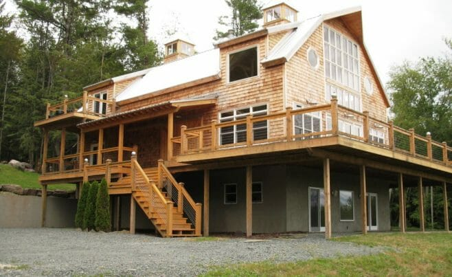 Exterior of Timber Frame Gambrel with Huge Windows and a Wrap Around Porch