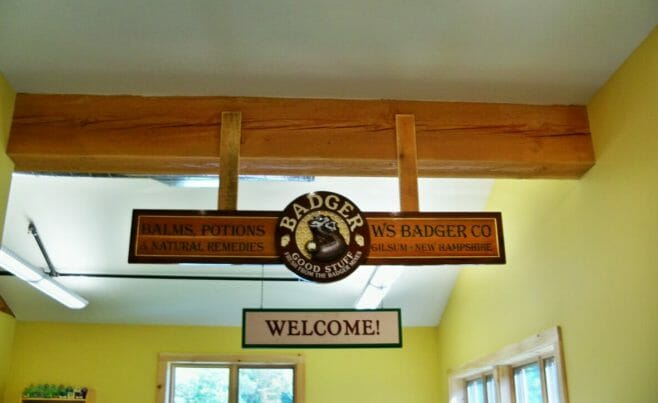 Badger Balm Welcome Sign Hanging from a Douglas Fir Beam