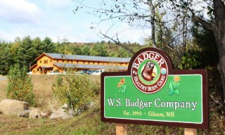 Badger Balm Welcome Sign with Completed Timber Frame Building Exterior in the Background