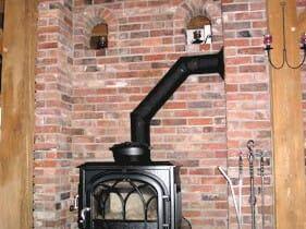 Brick Wall, Timber Beams, and a Black Fireplace