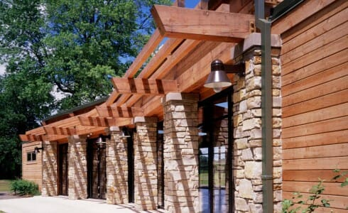 Timber Building at Citizen's Park With a Beautiful Overhang and Stone Columns