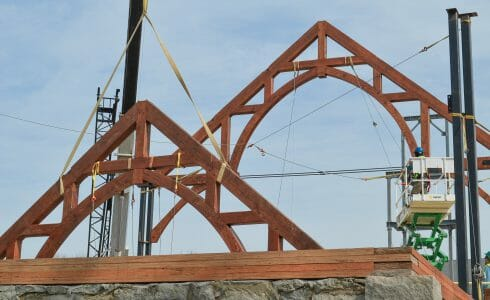 Arched Trusses being raised while constructing the timber frame for The Church of St. Michael the Archangel