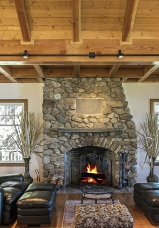 A stone fireplace in a Timber Frame Home. The Wakenah Great Room.