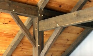 Timber Post with Brace and Rafter tie with traditional joinery in a timber frame home