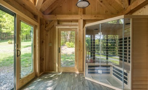 A Sauna in an workout room barn with heavy timber posts and beams