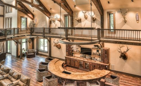 Interior of a Custom Timber Frame Residence in WI with dark stained, arched king post trusses, cathedral windows and ceilings, and a stone fireplace.