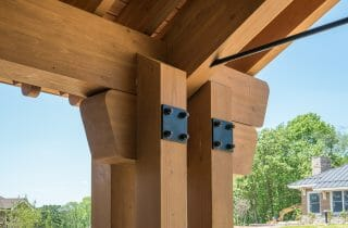 The Mahamudra Buddhist Retreat in Cragsmoor, NY has a heavy timber entryway and interior trusses fabricated from Glulam and Douglas Fir. The entryway features scrolls and black steel.