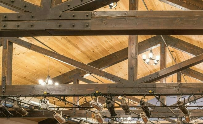 Timber Trusses with steel plates and mounted stage lights in a performance space in the Hopkinton Art Center