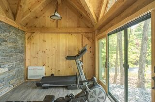 Exercise equipment in the Workout room and barn with stone wall and sliding glass doors, fabricated from rough sawn white pine