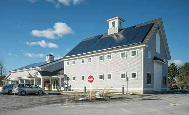 Exterior of The Hopkinton Art Center with solar panels and a white washed timber entry way