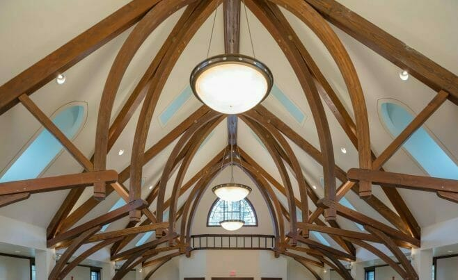 Finials on dark stained timber frame arches in a church sanctuary