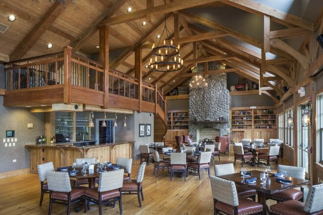 Interior of the South River Golf Club dining room and event space that features Timber Trusses, a Cathedral ceiling, and a tall stone fireplace.