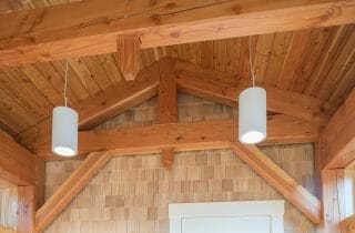 Douglas fir beams and trusses against a wood clad wall in the Port Society Complex
