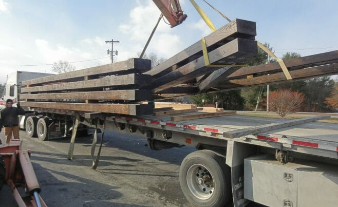 Timber Trusses being loaded onto a truck with a crane