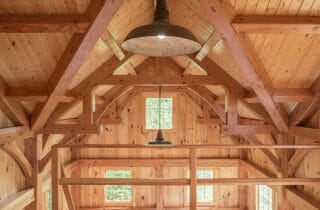 Loft area with heavy timber trusses in the Ox Hill Barn that overlooks the Cathedral Ceilings and windows in the Ox Hill Barn