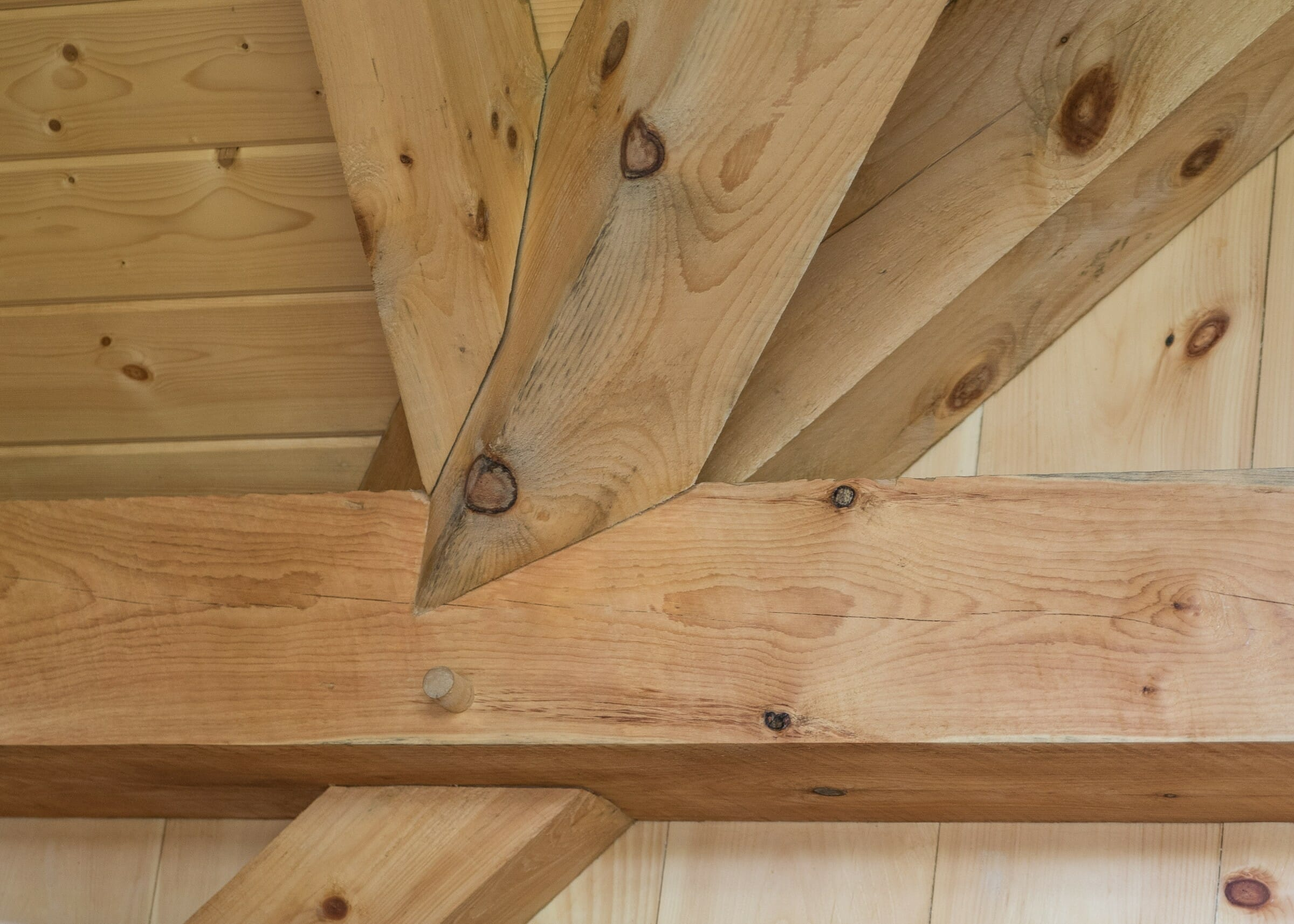 Complex joinery in a timber frame workout room made from rough sawn white pine