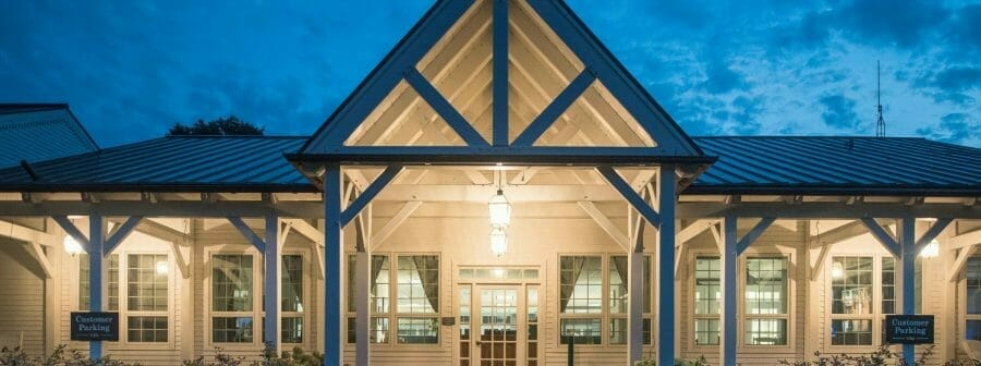 The VTel porch with post, beams, and king post trusses, has been fabricated with planed Douglas fir and painted white.