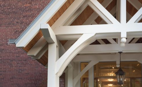 White Entry Canopy with king post trusses at Fuller Hall at the Vermont Academy school made with douglas fir