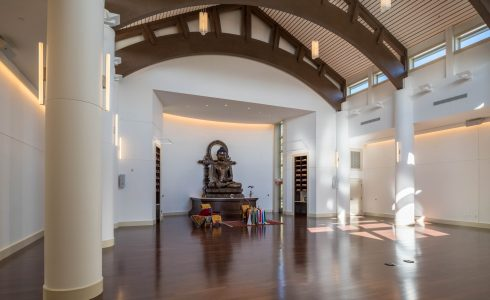 The Buddha statue in the Mahamudra Buddhist Center sits peacefully in the main hall with Timber Arches overhead