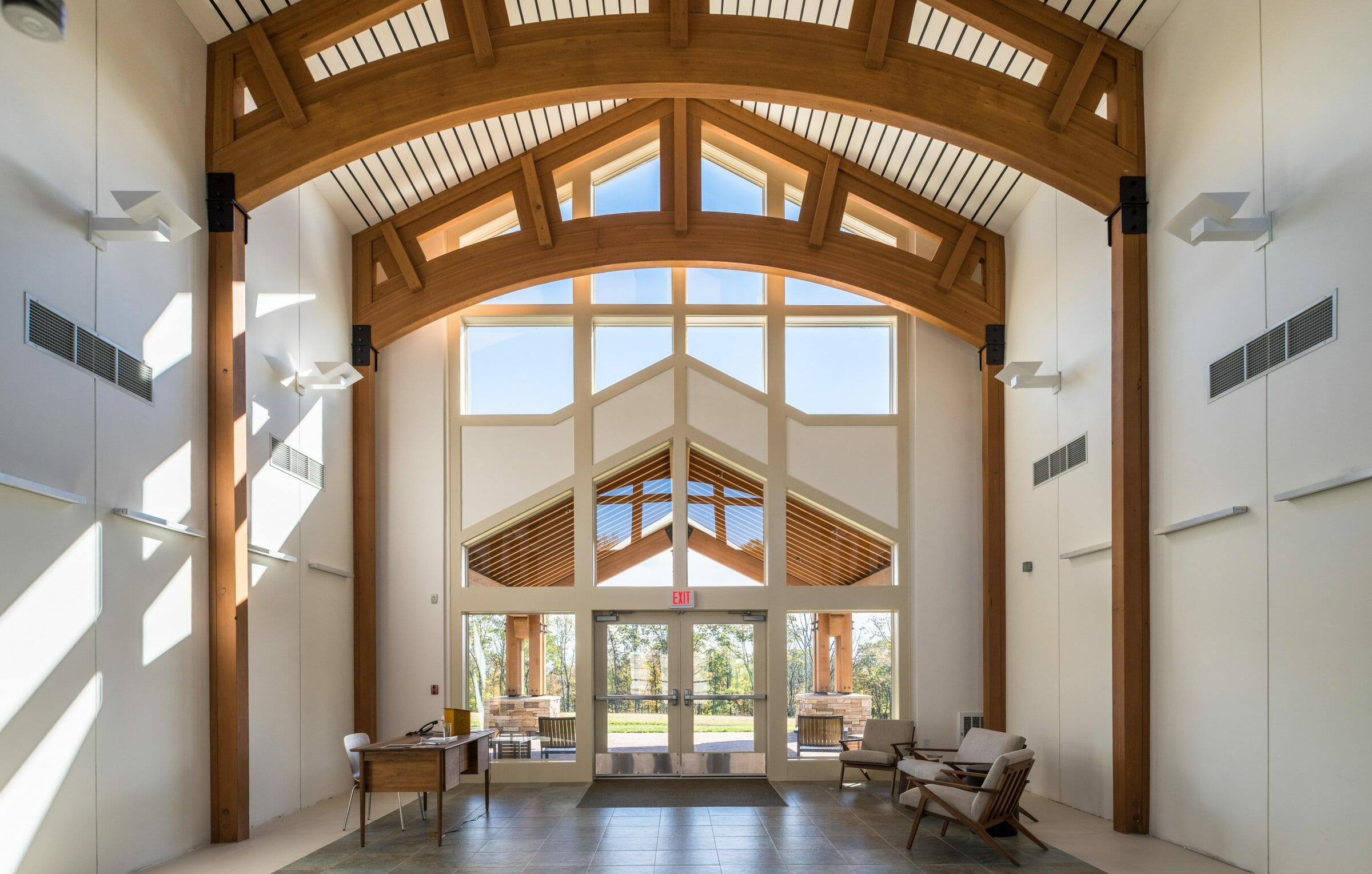 Interior of Mahamudra Buddhist retreat with high ceilings and glulam arches.