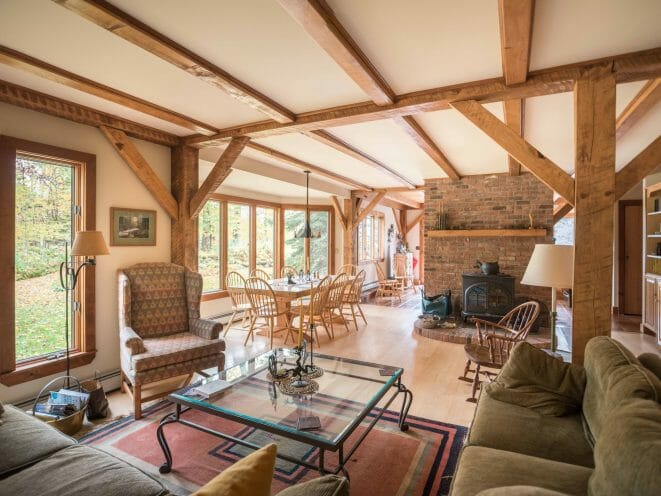 Vermont Retreat for sale with gathering room with wood posts and beams and stove and brick hearth