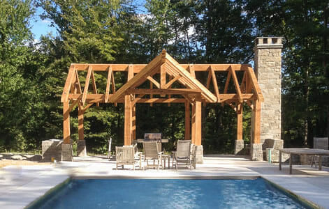 Pool House Timber Frame in CT. Pool patio with fireplace and rustic heavy timber pavilion.