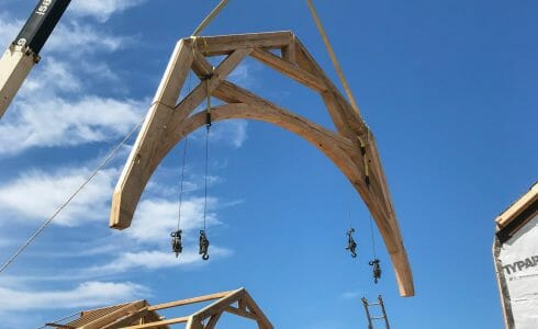 Lifting the reclaimed Oak Hammer Beam trusses by crane for the Seven Gates Residence in Martha's Vineyard