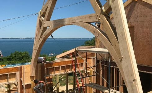 The reclaimed oak hammer beam truss being lowered into place by crane at the Seven Gates Residence in Martha's Vineyard