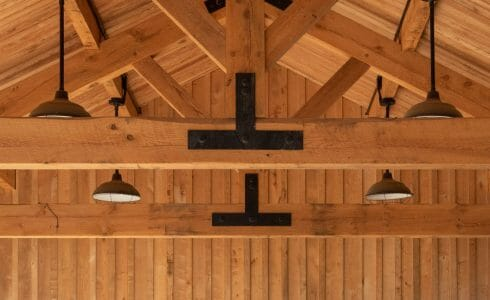 Timber Frame King Post Trusses with black steel plates in a pavilion at the Bechtel Summit home of the National Boy Scout Jamboree