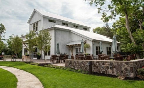 Exterior of the Briar Barn Inn in Rowley, MA. Built by Vermont Timber Works in the Monitor Barn Style. There is outdoor seating on the stone patio outside the barn.