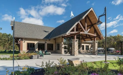 Exterior of the Adirondack Welcome Center in Queensbury, NY featuring Douglas fir Glulam Heavy Timber Trusses with steel plates.