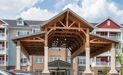 The Crossings at West Shore in Enola, PA. Timber Frame Porte Cochere Entry Way with Heavy Timber King Post Trusses and Stone Post Bases.