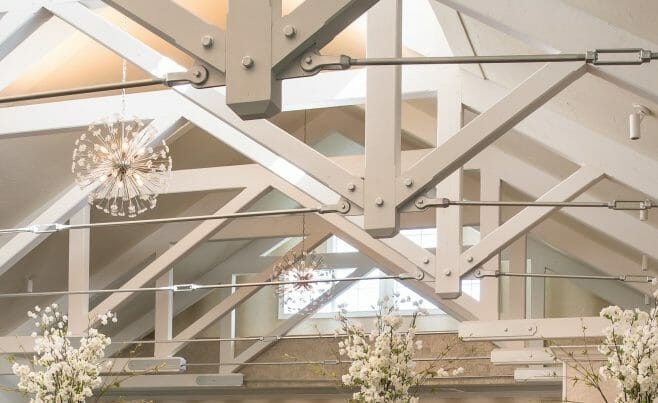 Steel tie bar and steel plate joinery details on a white timber truss in the Anya Restaurant in Thompson, CT.