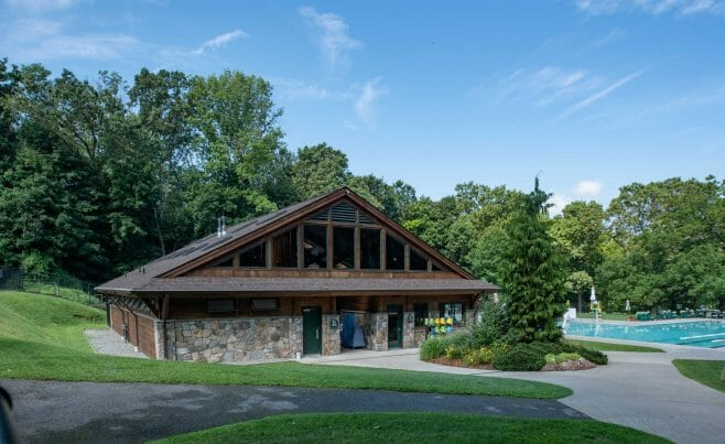 Exterior of the Katonah Pool house made with a heavy timber frame and trusses with stone post bases in Katonah New York.