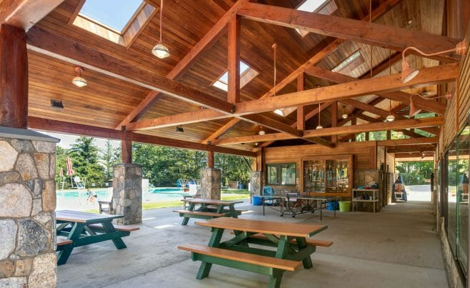 Interior of the Katonah Pool house made with a heavy timber frame and trusses with stone post bases in Katonah New York.