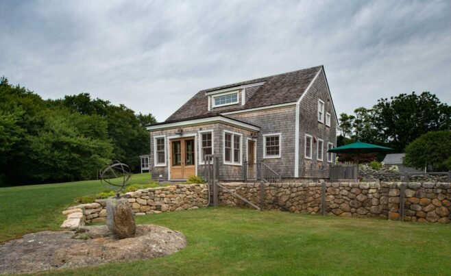 Exterior of a Guest Cottage in Martha's Vineyard overlooking the pool with traditional weathered Cedar siding